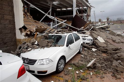 Cars parked next to an office supplies store partially destroyed by Hurricane Odile, in Los Cabos, Mexico, Monday, Sept. 15, 2014.