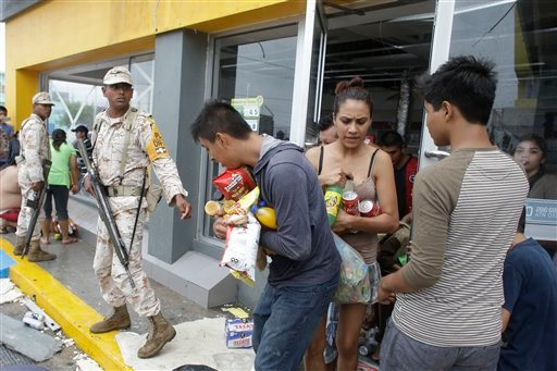 Mexican soldiers try to stop people from looting a convenience store destroyed by Hurricane Odile, in Los Cabos, Mexico, Monday, Sept. 15, 2014.