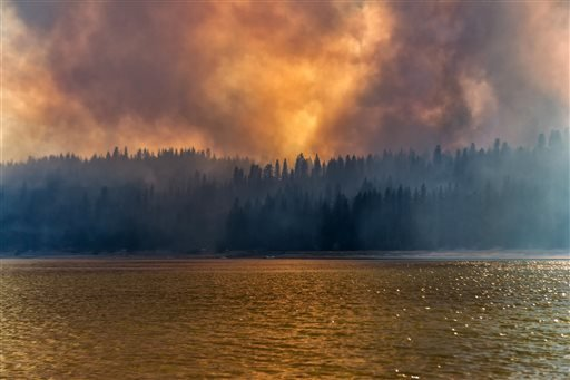 In this Sunday, Sept. 14, 2014 photo provided by YosemiteLandscapes.com, large plumes of smoke from a wildfire rise over Bass Lake, Calif.
