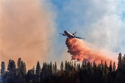 In this Sunday, Sept. 14, 2014 photo provided by YosemiteLandscapes.com, a DC-10 drops fire retardant over a wildfire at Bass Lake, Calif.