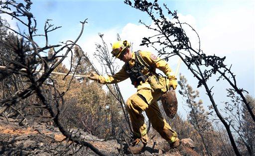 Firefighter Jesse Hadorowski climbs up steep terrain while battling a fire near Pollack Pines, Calif., Monday, Sept. 15, 2014.