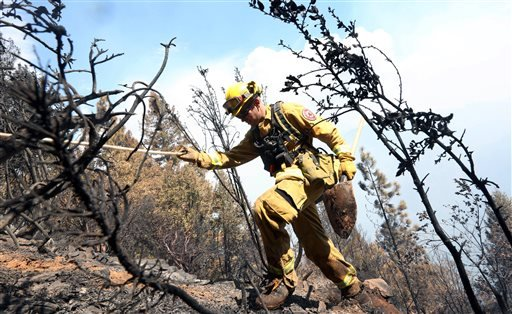 Firefighter Jesse Hadorowski climbs up steep terrain while battling a fire near Pollack Pines, Calif., Monday, Sept. 15, 2014.
