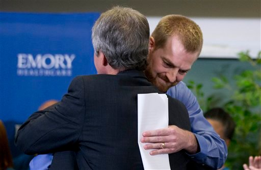 In this Aug. 21, 2014 file photo, ebola victim Dr. Kent Brantly, right, hugs a member of the medical staff that treated him, after being released from Emory University Hospital in Atlanta.
