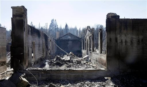 The smoldering empty shell of a local library and a Head Start center are all that remain Tuesday, Sept. 16, 2014, the day after a wildfire swept through Weed, Calif. (AP Photo/Rich Pedroncelli)