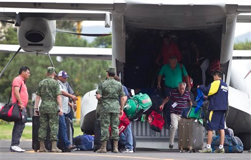 Mexican and foreign tourists arrive at an Air Force hangar in Mexico City after being airlifted out of the hurricane-ravaged resort area of Los Cabos by the Mexican armed forces Sept. 16, 2014. (AP Photo/Christian Palma)