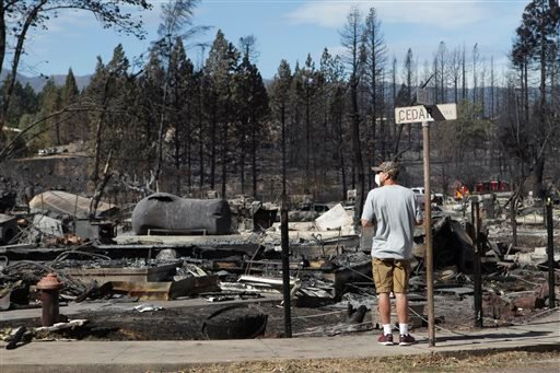 Jeremy Keen looks at his in-laws' home was destroyed in the Boles Fire in Weed, Calif. Wednesday, Sept. 17, 2014. Keen's home across the street was spared. (AP Photo/Record Searchlight, Andreas Fuhrmann)