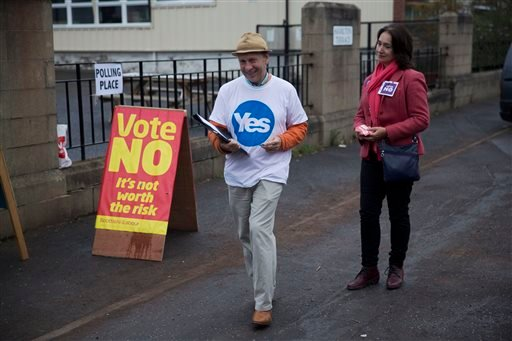 A Yes campaigner and a No campaigner stand outside a polling place in Edinburgh, Scotland, Thursday, Sept. 18, 2014. (AP)