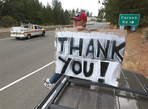 Herve Leconte sits atop his vehicle to display a sign thanking all those who are dealing with the King fire while park alongside Highway 50 near Camino, Calif., Thursday, Sept. 18, 2014. (AP Photo/Rich Pedroncelli)