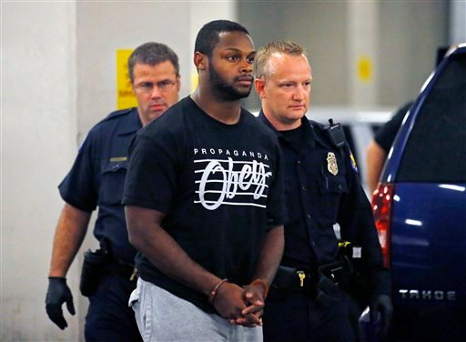 Phoenix police officers escort Arizona Cardinals running back Jonathan Dwyer, to the 4th Avenue Jail following his arrest, Wednesday, Sept. 17, 2014 in Phoenix. (AP)