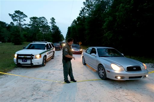 A Gilchrist County sheriff's deputy lowers the yellow tape to let vehicles through at the scene of a shooting on Thursday, Sept. 18, 2014 in Bell, Fla.