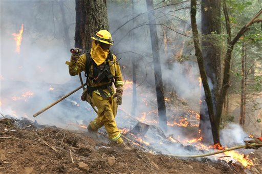 A firefighter pulls a hose over to battle flames approaching a containment line, while fighting the King fire near Fresh Pond, Calif., Thursday, Sept. 18, 2014.