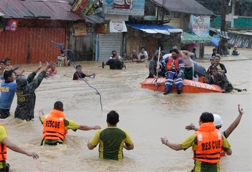 Rescuers use a rubber dinghy to rescue trapped residents after heavy monsoon rains spawned by tropical storm Fung-Wong flooded Marikina city, east of Manila, Philippines and most parts of the metropolis Friday, Sept. 19, 2014.