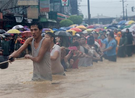 Residents use a rope to cross through deep floodwaters after heavy monsoon rains spawned by tropical storm Fung-Wong flooded Marikina city, east of Manila, Philippines and most parts of the metropolis Friday, Sept. 19, 2014.