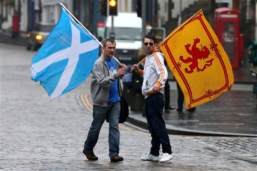Supporters of the Yes campaign for the Scottish independence referendum stand on the Royal Mile in Edinburgh, Scotland, Friday, Sept. 19, 2014.