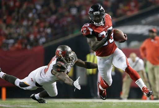 Atlanta Falcons running back Antone Smith (35) moves past Tampa Bay Buccaneers free safety Dashon Goldson (38) during the second half of an NFL football game, Thursday, Sept. 18, 2014, in Atlanta. Smith scored a touchdown on the play.