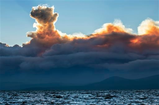 This Wednesday, Sept. 17, 2014 photo shows smoke from a California wildfire rising behind Lake Tahoe as seen from the Nevada side of the lake near Incline Village, Nev.