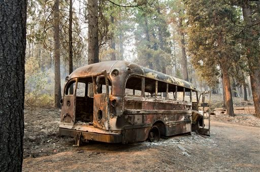 A burned out bus is shown near one of several homes that burned in the recent King fire near Icehouse in El Dorado County on Friday, Sept. 19, 2014. (AP Photo/The Sacramento Bee, Randall Benton)