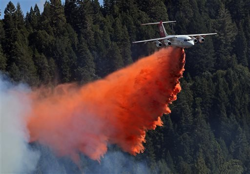 In this Sept. 15, 2014 file photo, a an aerial tanker drops its load of fire retardant on the King fire near Pollack Pines, Calif.