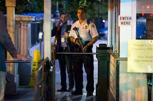 A Secret Service police officer holds a weapon as he stands near an entrance to the White House complex during an evacuation minutes after President Barack Obama departed Washington for Camp David aboard Marine One on Friday, Sept. 19, 2014.
