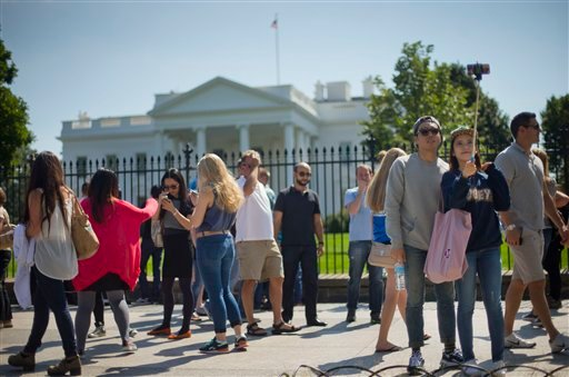 Tourist stop to take their photograph in front of the White House in Washington, Saturday, Sept. 20, 2014.