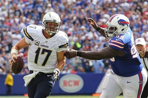 San Diego Chargers quarterback Philip Rivers (17) scrambles away from Buffalo Bills defensive tackle Marcell Dareus (99) during the first half of an NFL football game, Sunday, Sept. 21, 2014, in Orchard Park, N.Y. (AP Photo/Bill Wippert)