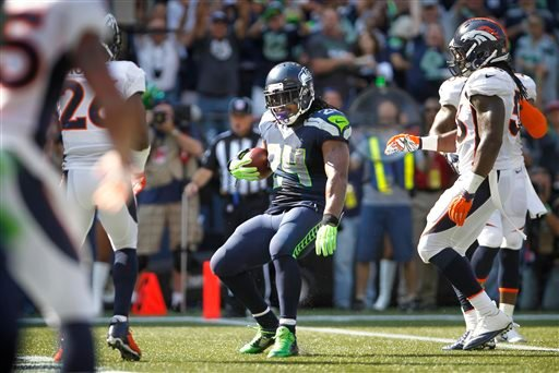 Seahawks running back Marshawn Lynch (24) steps into the end zone after catching a pass for a touchdown in the first half of an NFL football game against the Denver Broncos, Sunday, Sept. 21, 2014, in Seattle. (AP Photo/The Olympian, Tony Overman)