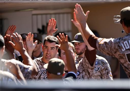 San Diego Padres' Seth Smith celebrates with teammates after scoring on a sacrifice fly by Alexi Amarista against the San Francisco Giants during the fifth inning of a baseball game Sunday, Sept. 21, 2014, in San Diego. (AP Photo/Don Boomer)