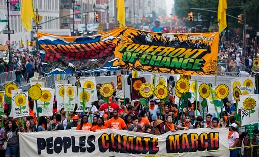 People gather near Columbus Circle before the People's Climate March in New York Sunday, Sept. 21, 2014. Thousands of people from across the nation are expected to participate in what's billed as the largest march ever on global warming.