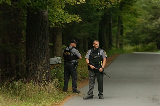 Pennsylvania State Troopers walk along a wooded area on Bear Town Road near Route 447 in Barrett Township on Saturday, Sept. 20, 2014, near Canadensis, Pa., during a search for suspected killer Eric Frein.