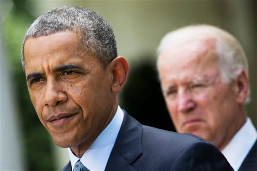 In this June 30, 2014, file photo, President Barack Obama, accompanied by Vice President Joe Biden, pauses while making a statement about immigration reform, in the Rose Garden of the White House in Washington.