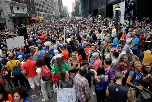 People fill 58th Street between 8th and 9th Avenue in New York before a climate change protest march Sunday, Sept. 21, 2014.