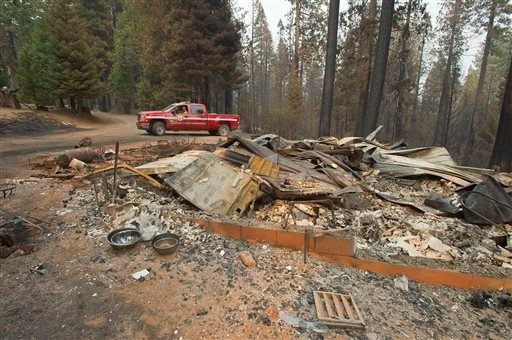 In a Friday, Sept. 19, 2014 file photo, a truck passes one of several homes that burned in the recent King fire near Icehouse in El Dorado County, Calif.