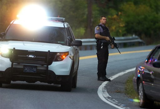 A Pennsylvania State Trooper stands with his weapon ready on Route 447 in Price Township on Sunday, Sept. 21, 2014 near Canadensis, Pa., during a massive search for suspected killer Eric Frein. (AP Photo / The Scranton Times-Tribune, Butch Comegys)