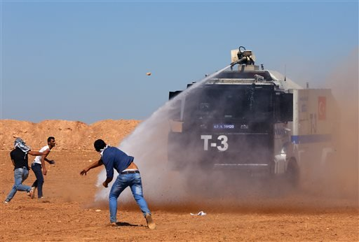 Turkish security forces use teargas and water cannons to disperse protesting local people as several hundred Syrian refugees wait at the border in Suruc, Turkey, Sunday, Sept. 21, 2014. (AP)