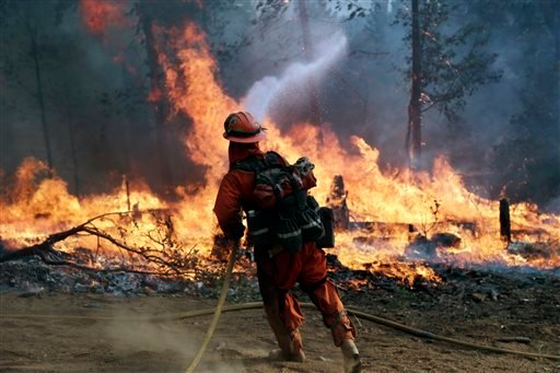 A firefighter with the Gabilan Camp crew hoses down hot spots during a controlled burn to fight the King Fire on Monday, Sept. 22, 2014, near Placerville, Calif.
