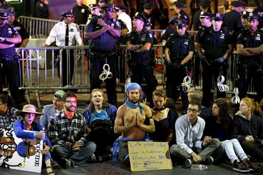 Protesters sit at the intersection of Wall St. and Broad St. in New York, Monday, Sept. 22, 2014.