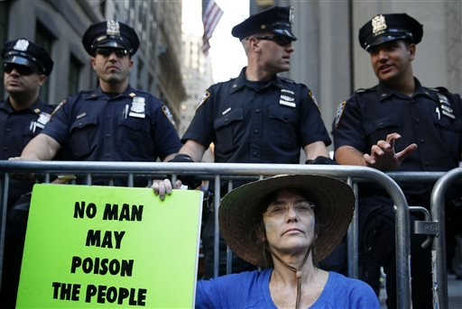 A protester sits on the street behind a barricade lined with police officers at the entrance to Wall St. in New York, Monday, Sept. 22, 2014.