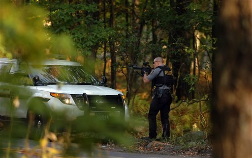 A Pennsylvania state trooper draws his weapon in a wooded area on Snow Hill Road in Price Township, Pa., during a huge manhunt for suspected killer Eric Frein on Sunday, Sept. 21, 2014, near Canadensis, Pa.