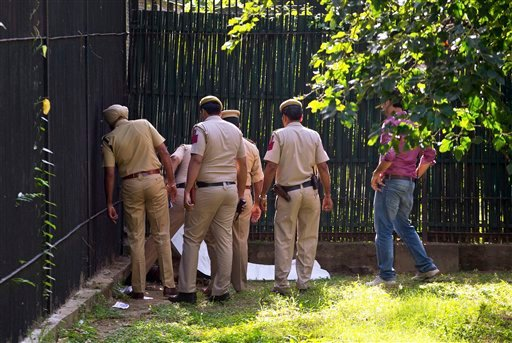 Policemen inspect the body of a man who was killed by a white tiger at the zoo in New Delhi, India, Tuesday, Sept. 23, 2014.