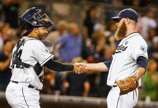 San Diego Padres catcher Rene Rivera, who drove in the only run of the game, congratulates relief pitcher Kevin Quackenbush after the final out of the Padres' 1-0 victory over the Colorado Rockies in a baseball game Monday, Sept. 22, in San Diego.