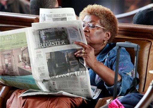 In this April 16, 2014 file photo, Dorothy Shumrt reads the Los Angeles Register newspaper on the day of it's launch while waiting for a train at Union Station, in Los Angeles.