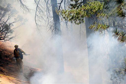 A firefighter is surrounded by smoke while fighting the King Fire on Tuesday, Sept. 23, 2014, in Mosquito, Calif. (AP Photo/Marcio Jose Sanchez)