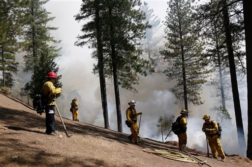 Firefighters hold the line along a containment area while fighting the King Fire on Tuesday, Sept. 23, 2014, in Mosquito, Calif. (AP Photo/Marcio Jose Sanchez)
