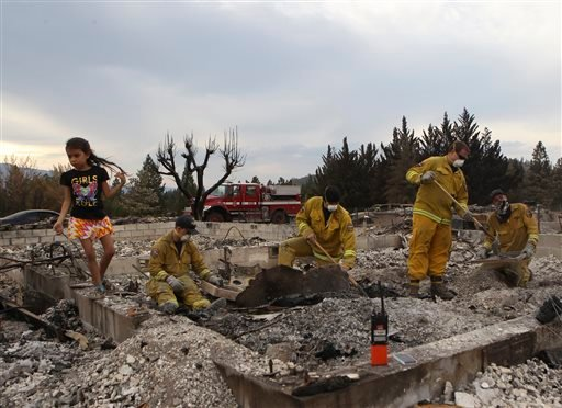 Arely Yerena plays while Cal Fire firefighters Cole Roberts, from left, Luke Woodward, engineer Aaron Gaeddert and firefighter Mike Raffaini sift through he ashes at her family's house in Weed, Calif. (AP Photo/Record Searchlight, Greg Barnette)