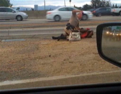 In this July 1, 2014 file video image provided by motorist David Diaz, a California Highway Patrol officer straddles a woman while punching her on the shoulder of a Los Angeles freeway. (AP Photo/David Diaz, File)