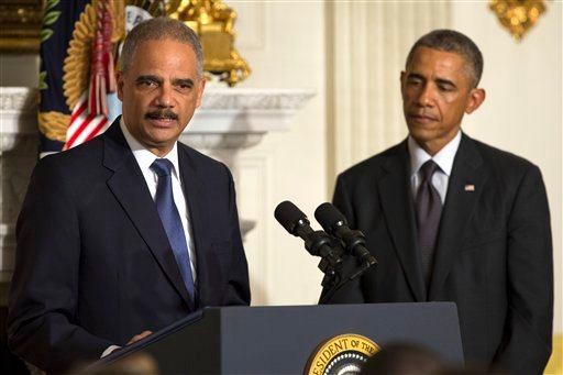 President Barack Obama, right, looks on as Attorney General Eric Holder speaks in the State Dining Room of the White House, on Thursday, Sept. 25, 2014, in Washington.
