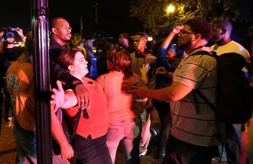 Two protesters protect a man at far left who had words with other protesters as they marched on S. Florissant Road in Ferguson on Thursday, Sept. 25, 2014. (AP Photo/St. Louis Post-Dispatch, Robert Cohen)