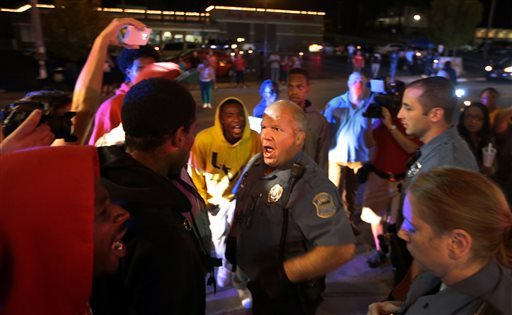 Protesters exchange words with a Ferguson police officer who was moving them off the street in front of the Ferguson Police Department, as they called for the resignation of Chief Tom Jackson on Thursday, Sept. 25, 2014.