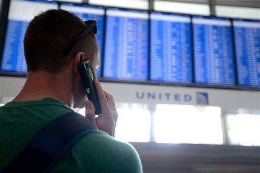 Dennis McCormack of Rockaway, N.J. checks the departure board only to find out that his flight to Newark, N.J. has been canceled at O'Hare International Airport in Chicago, Friday, Sept. 26, 2014.
