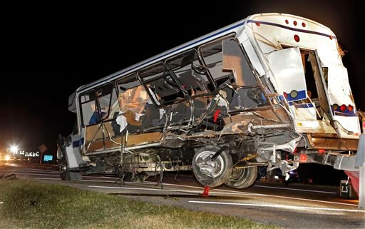 A wrecker removes the team bus as Highway Patrol and emergency personnel work the scene of a fatality accident just south of the Turner Falls area.on Saturday, Sept. 27, 2014 in Davis, Okla.